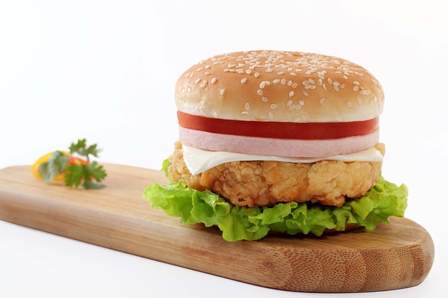 layered burger on top of wooden board