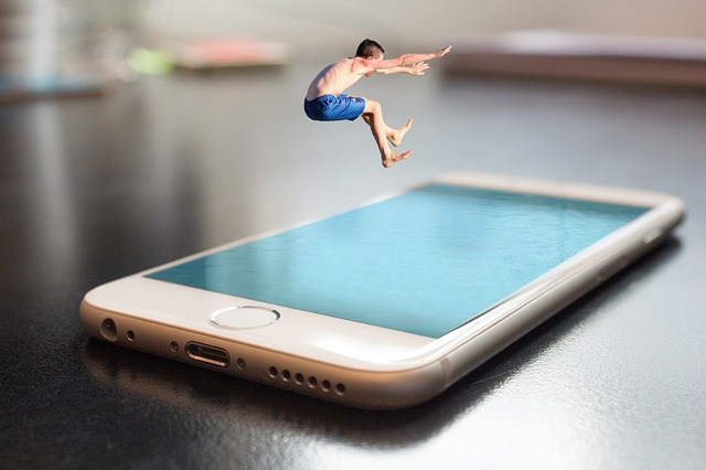 Miniature man jumping into a phone blue screen